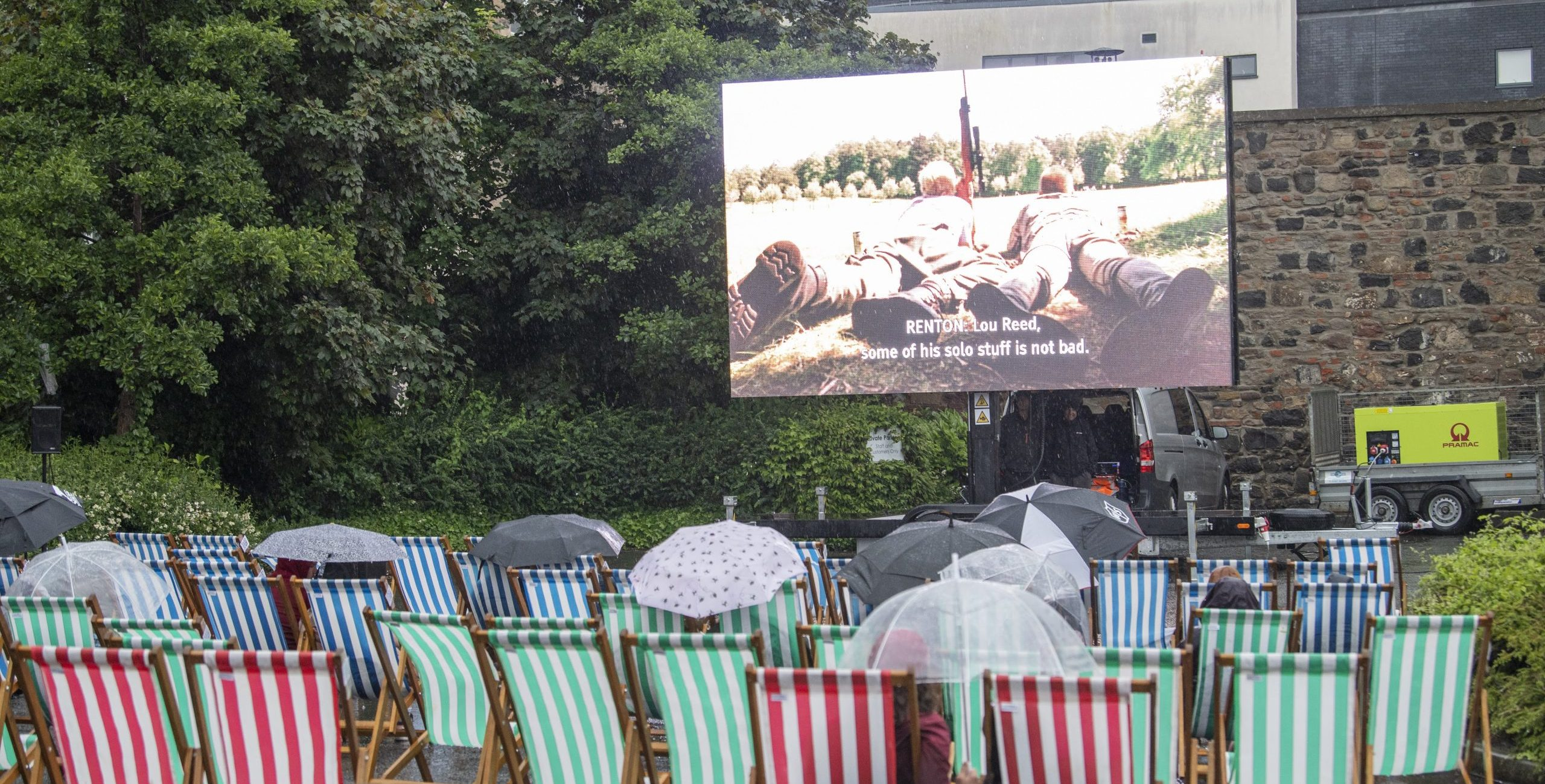 A group of striped deckchairs face away from the camera. They are pointed towards a screen showing Trainspotting on a rainy day in Edinburgh.