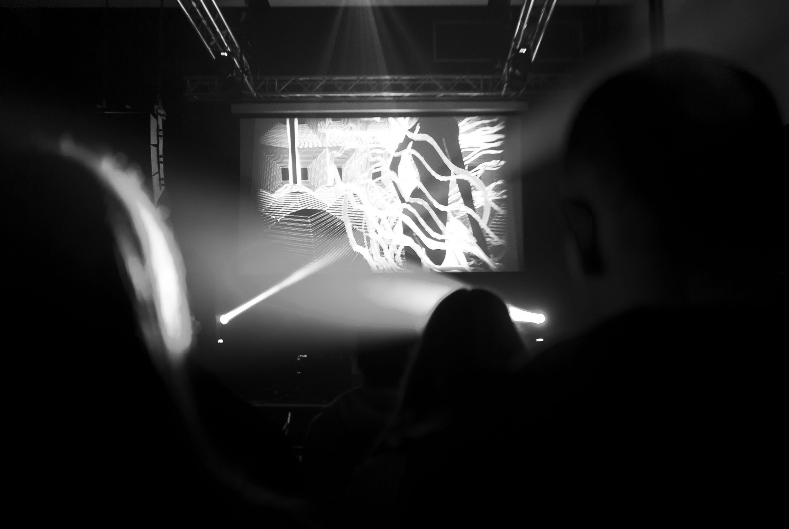An abstract black-and-white photograph of a performance, with a screen beaming visuals towards an audience.
