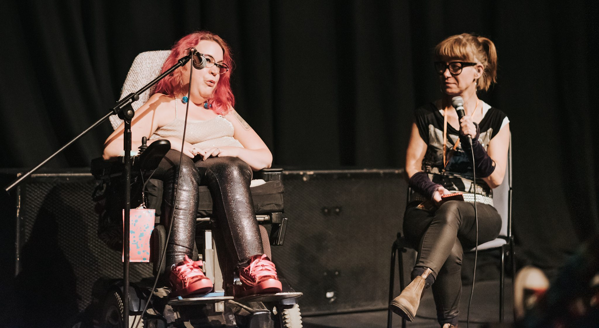 Two people talk on a stage at a film event. The person on the left uses a wheelchair, and has pink hair. The person on the right has blonde hair and sits in a chair. Both people are talking into microphones.