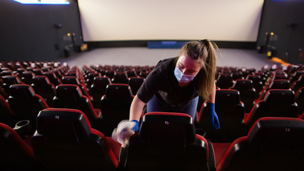 A person cleans a cinema seat with disinfectant. They wear a mask and stand in an empty cinema.