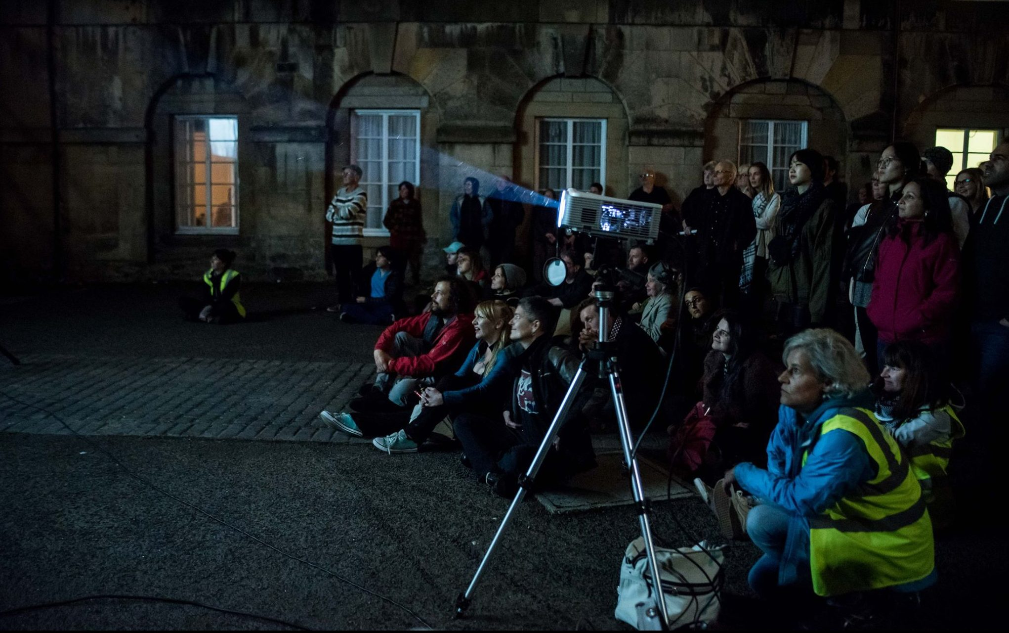 An audience sits on the floor outside, looking towards a projection that's happening off screen. A projector beams light to the left of the image.