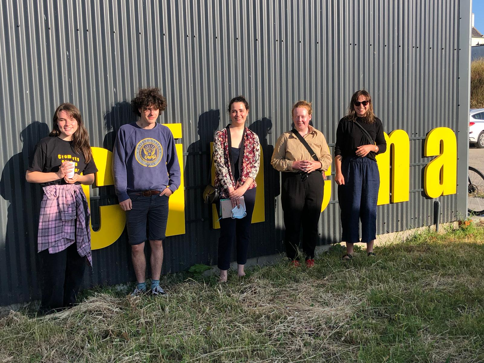 The Cromarty young programmers group stand in front of a building, with cinema written on the side in big yellow letters.