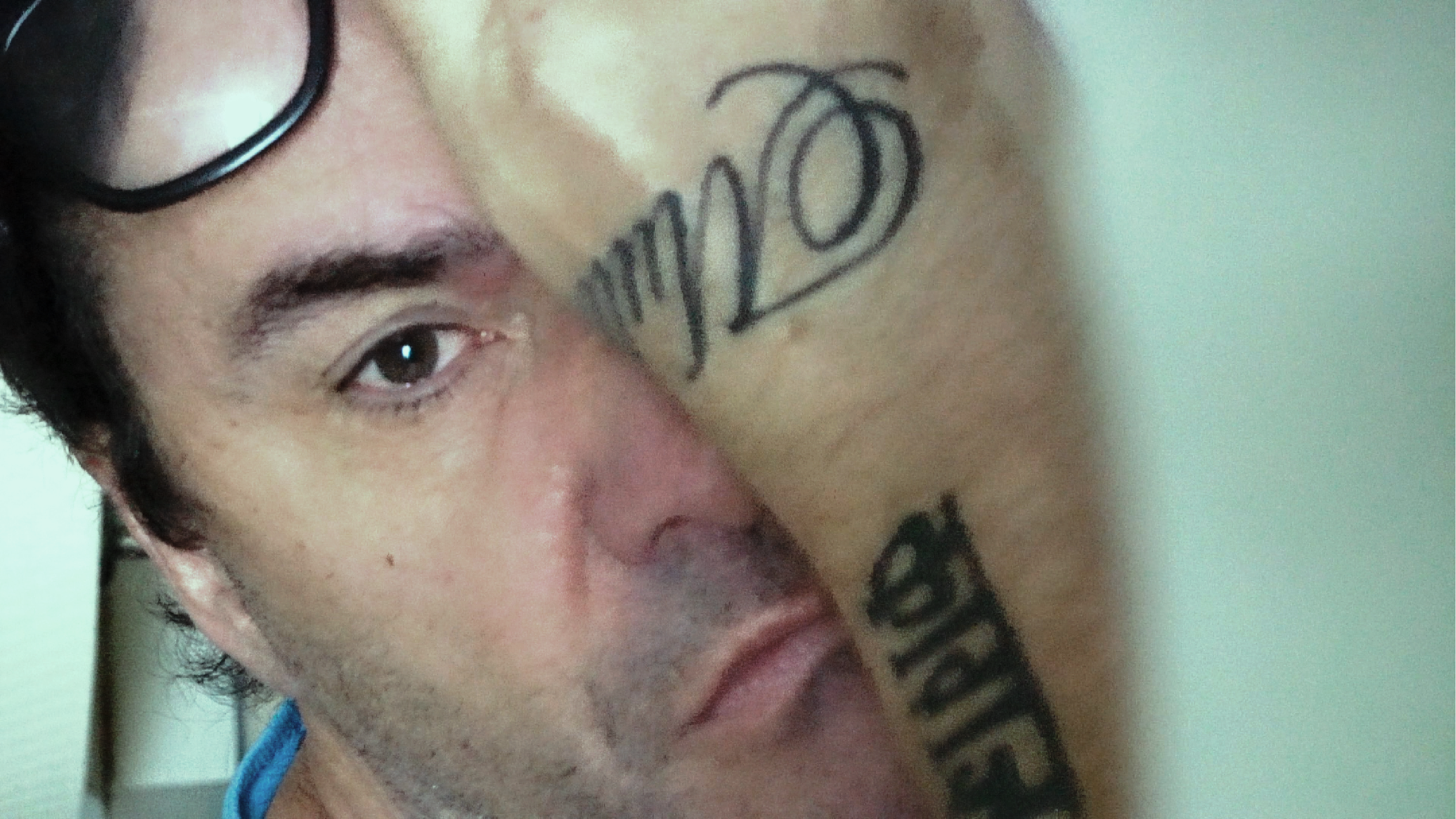A man's face is half-obscured by his arm. The man has glasses perched on top of his head, and tattoos on the arm covering his face.
