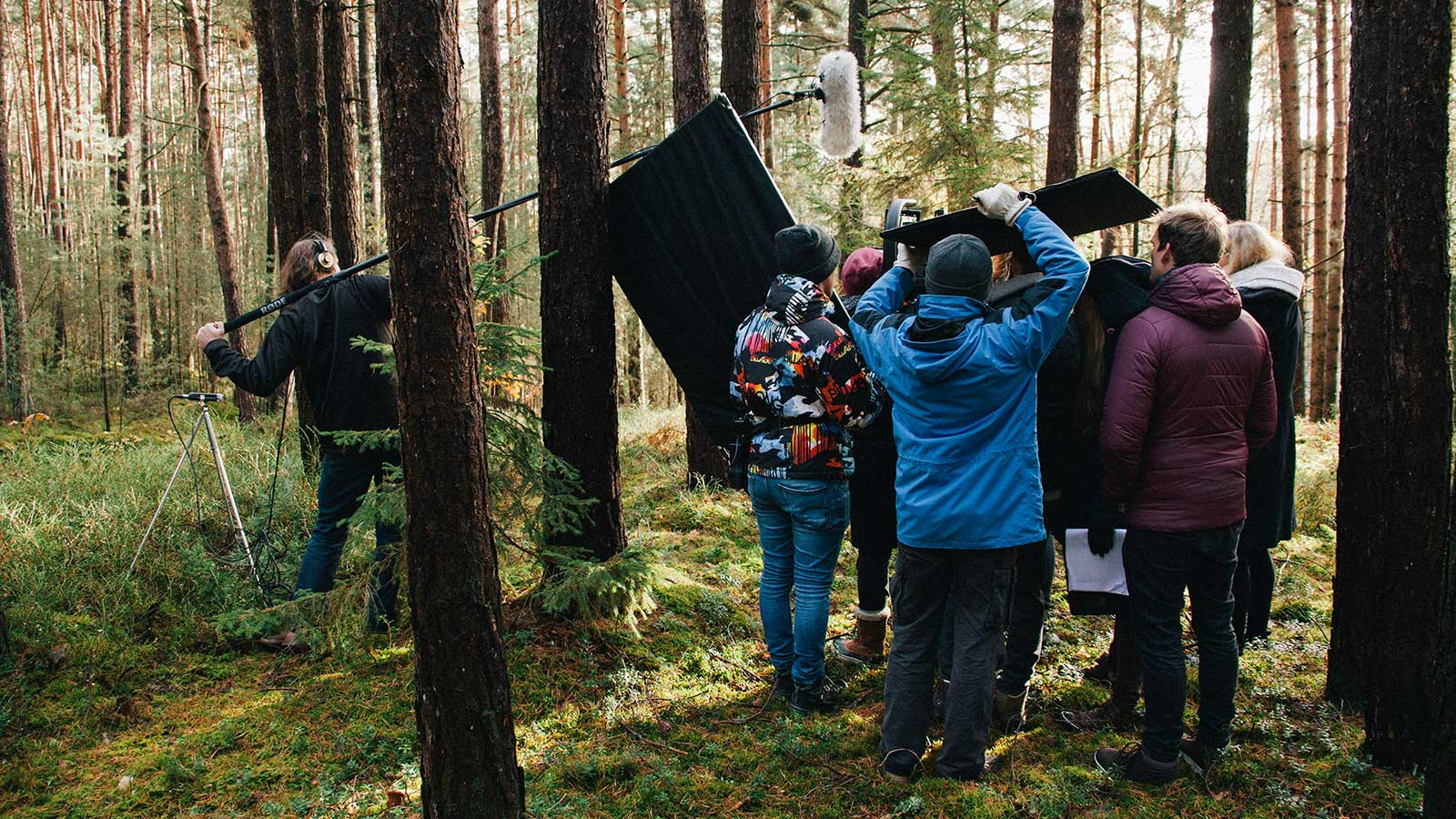 A group of people stand outside filming in a forest.